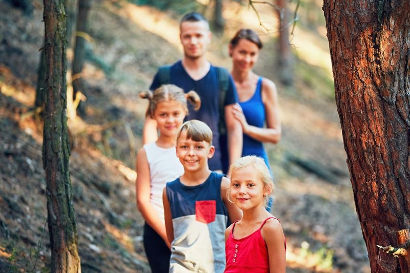 Children Family Tourist Travel Trip Boys Child Childhood Daughter Father Forest Forest Photography Front View Girl Happiness Journey Looking At Camera Mother Parents Portrait Smiling Son Togetherness Tourism Tree Trunk