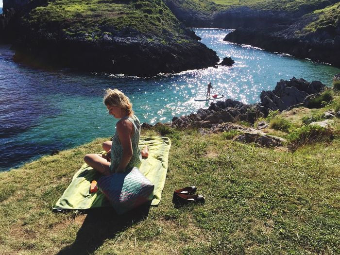 High angle view of woman sitting on blanket at playa de cue