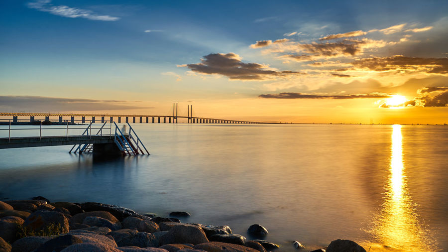 Beauty In Nature Built Structure Calm Cloud Cloud - Sky Idyllic Nature No People Non-urban Scene Ocean Orange Color Outdoors Pier Reflection Rippled Scenics Sky Sun Sunset Tourism Tranquil Scene Tranquility Travel Destinations Water Wooden Post