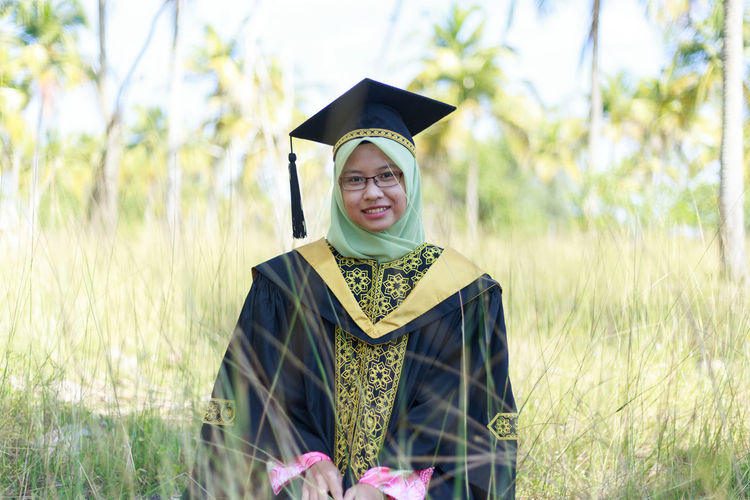 Portrait Of Young Woman Wearing Hijab And Graduation Gown Sitting Amidst Plants On Field At Park