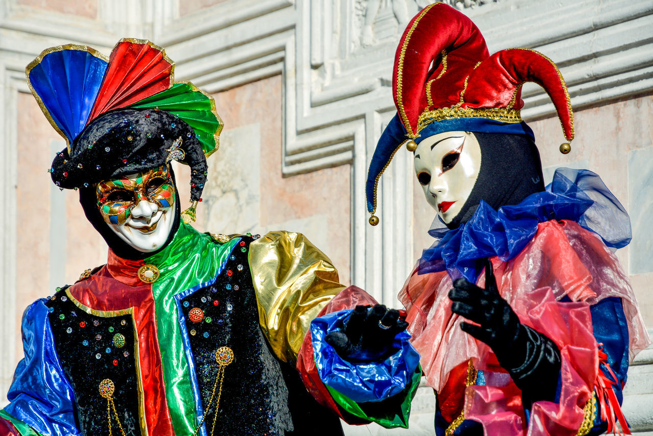 mask - disguise, carnival - celebration event, costume, multi colored, venetian mask, celebration, two people, disguise, real people, day, outdoors, standing, portrait, halloween, clown, close-up, people