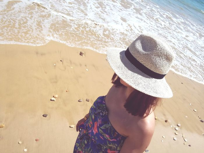 Woman wearing hat standing at beach during summer