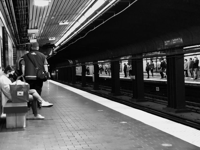 Rear view of people on railroad station platform