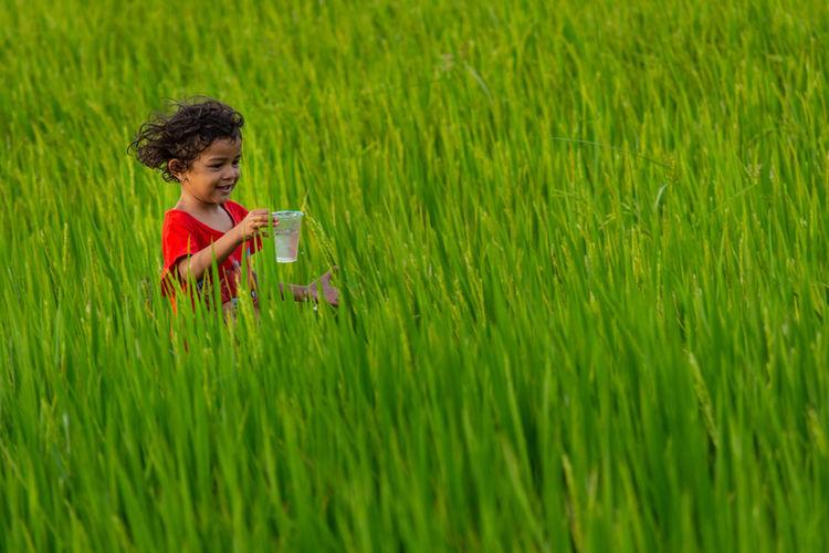 Girl holding glass on grassy field