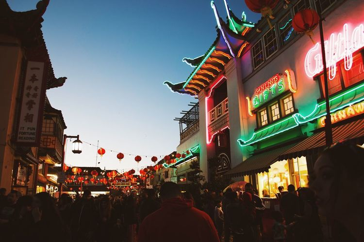 Crowd at illuminated city against sky