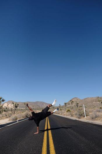 Full length of man doing stunt on road against clear sky