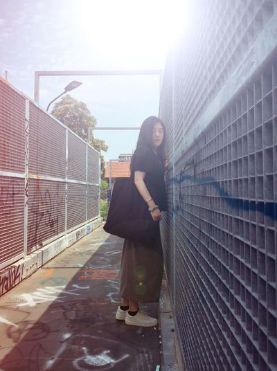 Low angle view of woman standing by wall