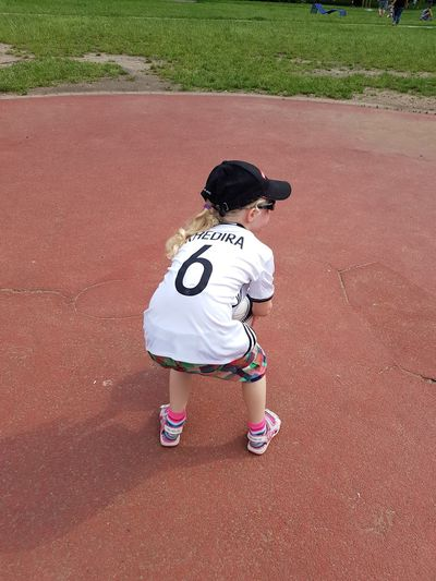 Rear view of girl holding soccer ball in park