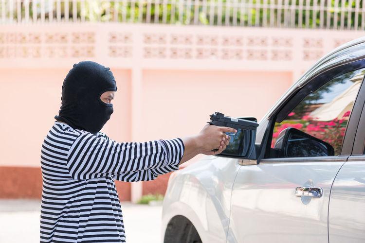 Thief pointing gun towards car in parking lot
