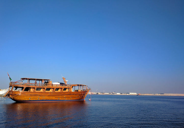 Ship in sea against clear blue sky