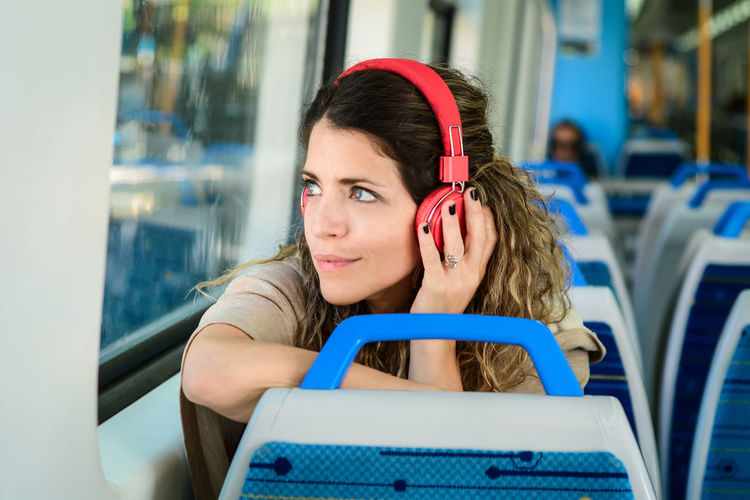 Close-up of beautiful woman looking away while listening to music in bus