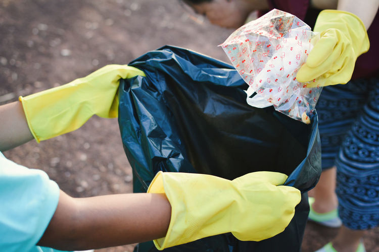 Cropped Hands Wearing Gloves Holding Garbage Bag At Park
