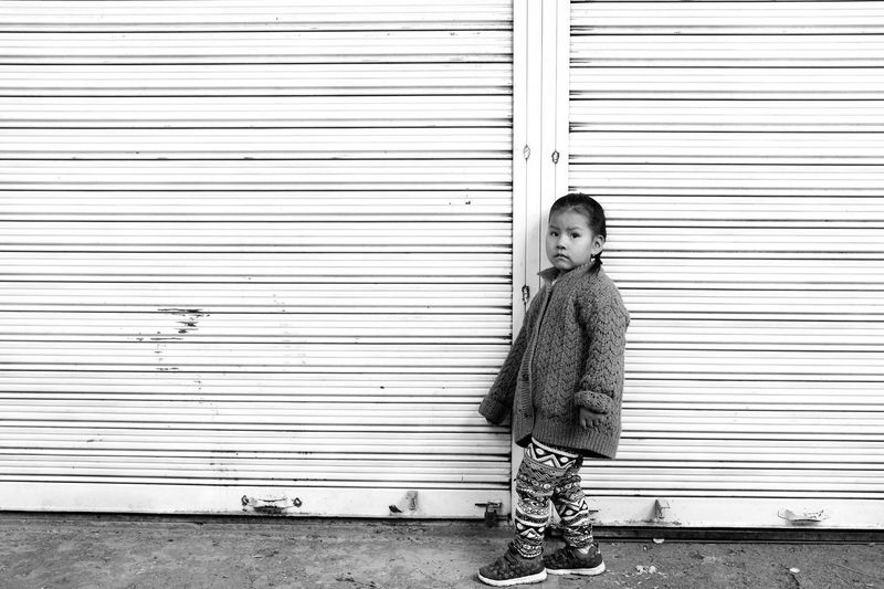 Portrait of boy standing against closed shutter