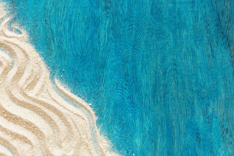 Summer time concept with starfish and sand on a blue wooden background
