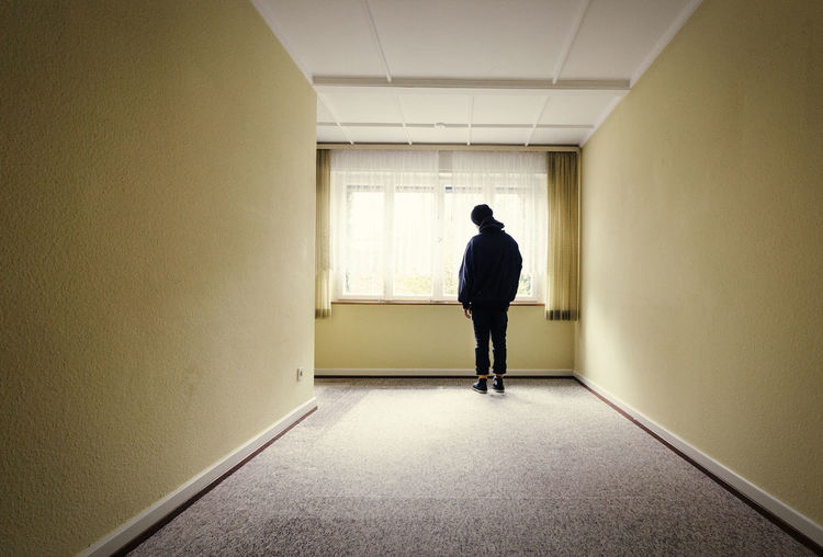 Rear view of man standing in corridor