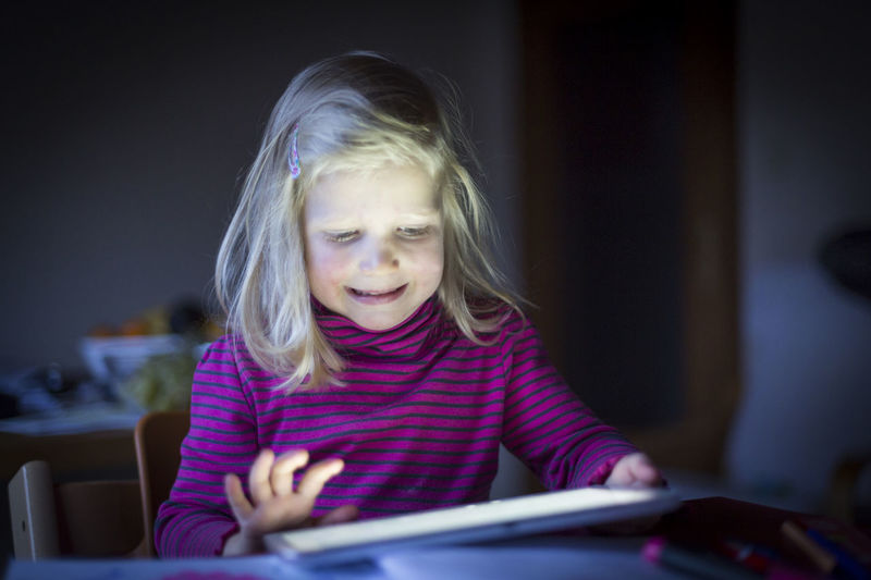 Girl Using Digital Tablet On Table At Home