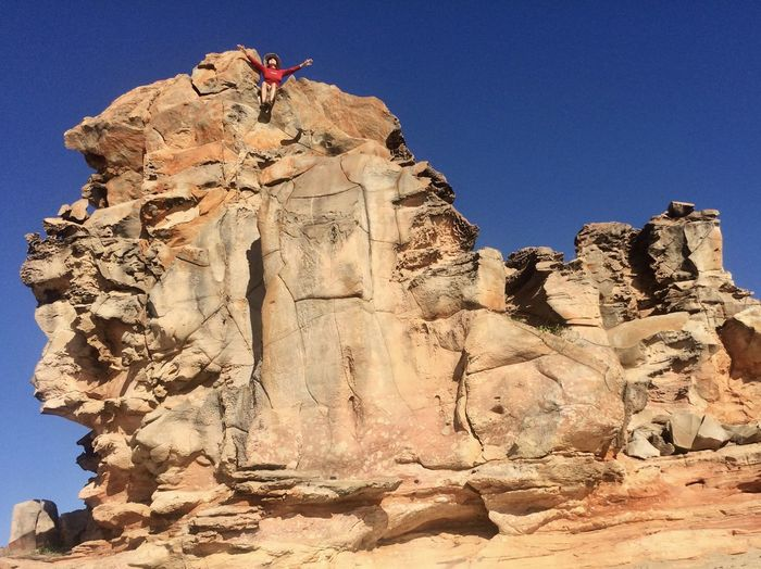 Low angle view of woman sitting on rock formation at desert during sunny day