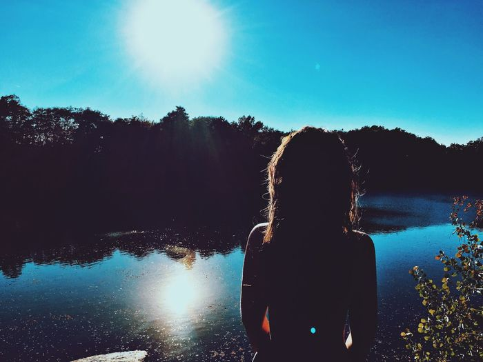 Woman Standing In Front Of Lake During Sunny Day