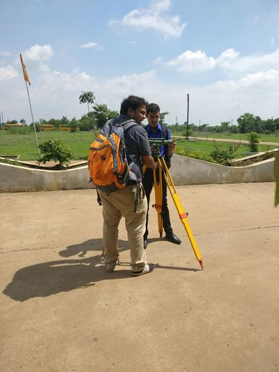 Man with backpack using surveyor on footpath against sky