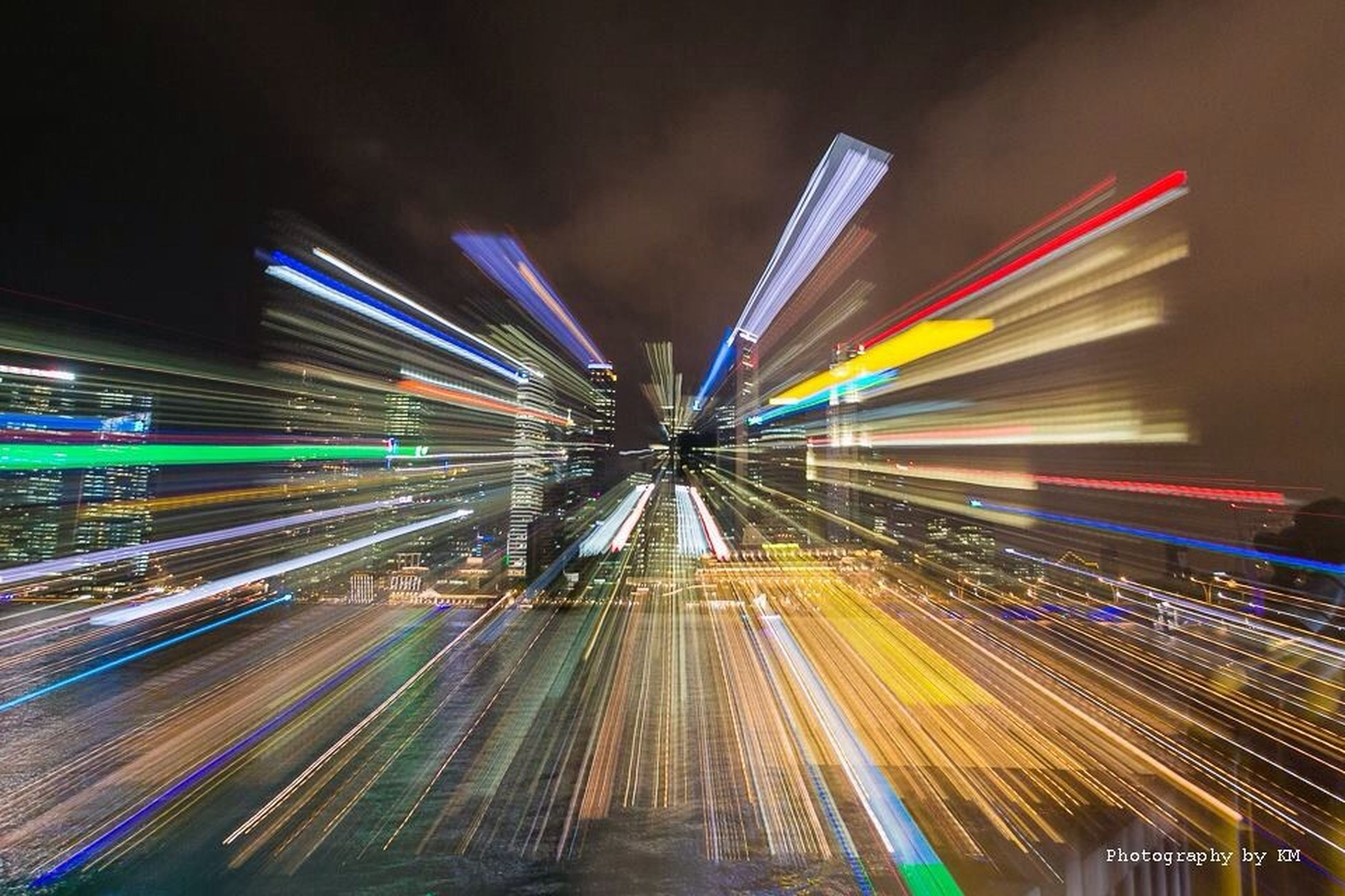 illuminated, night, long exposure, light trail, motion, transportation, blurred motion, speed, lighting equipment, architecture, multi colored, built structure, city, the way forward, diminishing perspective, city life, glowing, light - natural phenomenon, no people, road