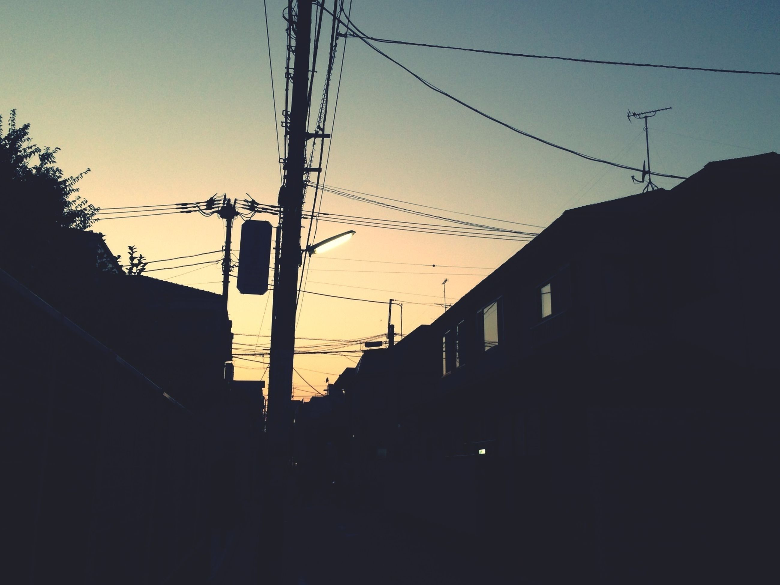 building exterior, power line, architecture, built structure, cable, electricity pylon, electricity, clear sky, low angle view, power supply, silhouette, house, sky, residential structure, residential building, fuel and power generation, sunset, connection, power cable, city