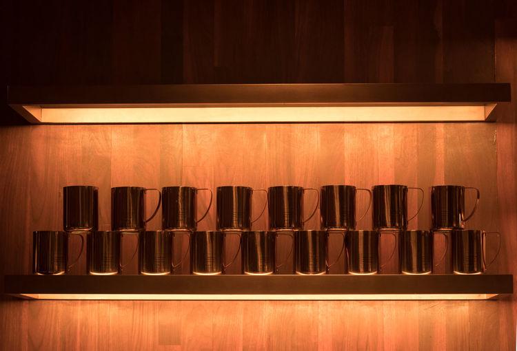 Mugs arranged side by side on shelf