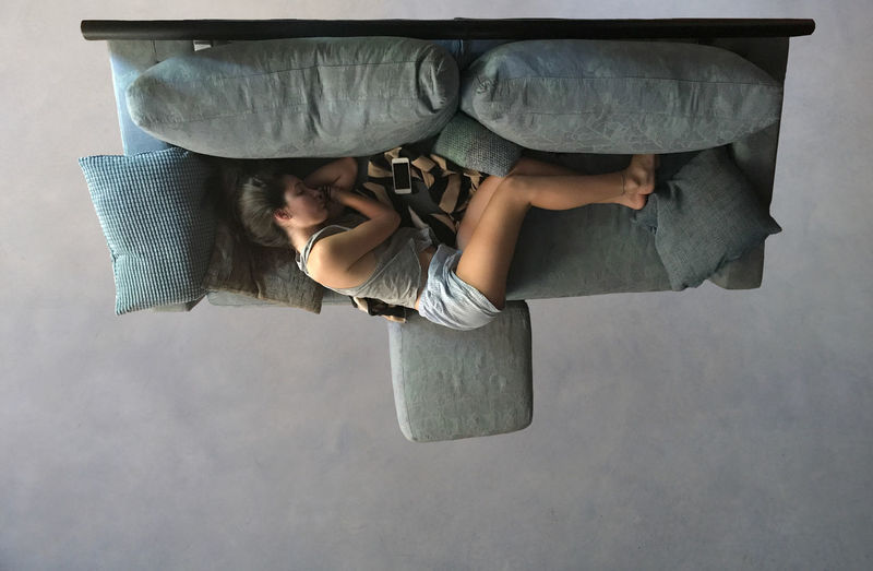 Directly above view of woman sleeping on sofa in living room at home
