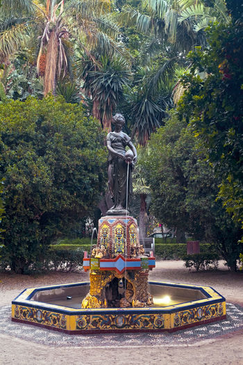 Malaga, Spain - June 24, 2018. The Ninfa del Cantaro is a Neoplateresque bronze statue and fountain located in a roundabout in the park of the Spanish city of Malaga, made in the year 1877. 1877 Fountain Malaga Neoplateresque Ninfa Del Cantaro Old Structures Palm Tree SPAIN Architecture Art And Craft Bronze Statue Creativity Day España Fountain Growth Human Representation Mode Of Transportation Motion Nature Ninfa No People Outdoors Plant Representation Roundabout Sculpture Statue Staue  Transportation Tree Water EyeEmNewHere Summer In The City