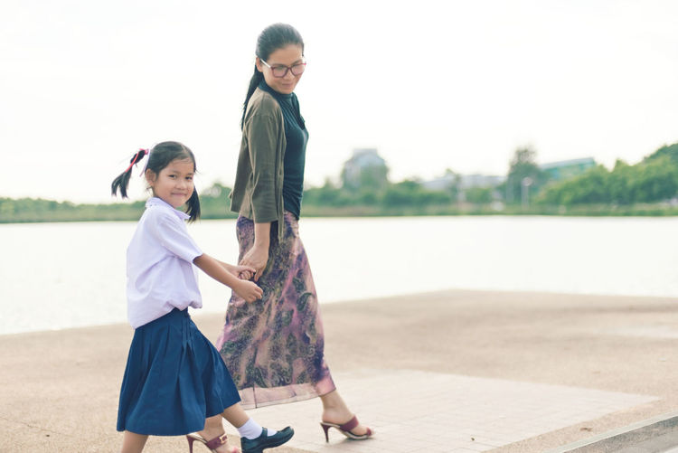 Mother & Daughter Casual Clothing Child Childhood Day Emotion Females Full Length Girls Innocence Lake Leisure Activity Looking At Camera Outdoors Park - Man Made Space Real People Smiling Standing Together Togetherness Two People Walking Women