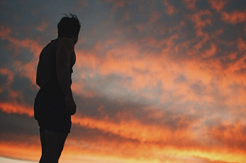 Low Angle View Of Man Standing Against Cloudy Sky During Sunset