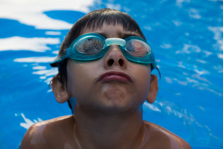 Close-up portrait of shirtless boy swimming in pool