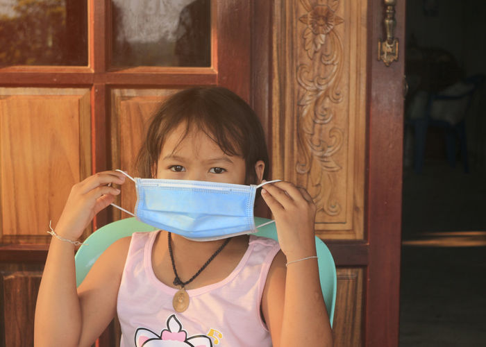 Portrait of girl wearing mask at home