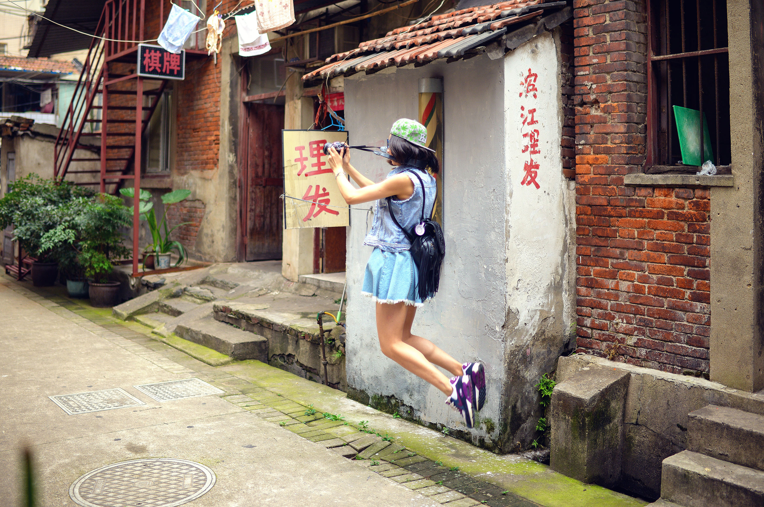 building exterior, full length, architecture, built structure, lifestyles, leisure activity, casual clothing, young adult, person, jumping, walking, street, wall - building feature, young women, day, sunlight, holding, side view