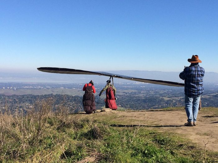Rear view of people with hand glider on mountain peak against clear sky