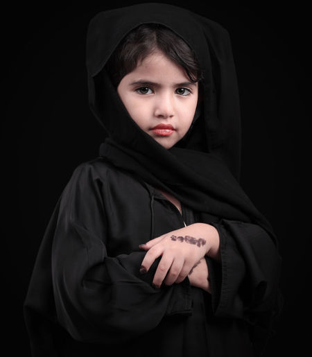 Portrait of girl in burka against black background