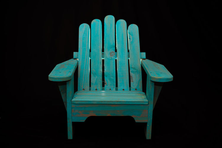 Close-up of blue chair against black background
