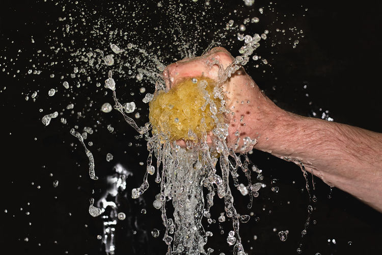 Close-up of man splashing water against black background