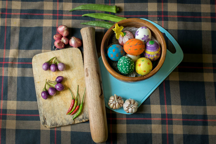 High angle view of multi colored easter eggs and vegetables on table