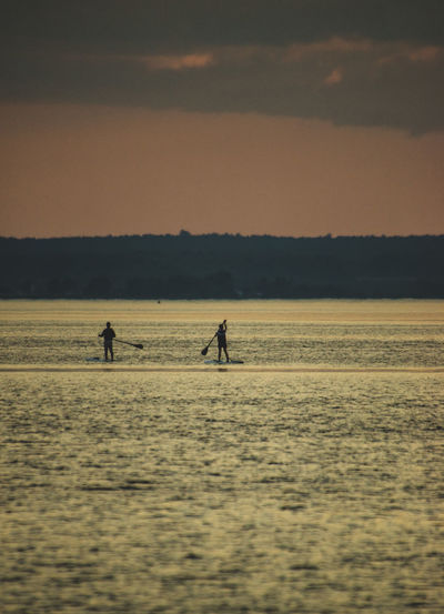 Silhouette people paddleboarding in sea against sky during sunset