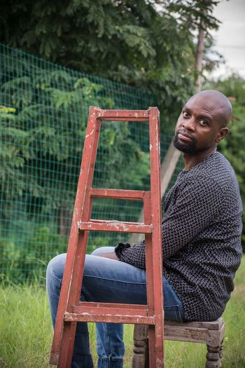 Portrait Of Man Sitting By Ladder