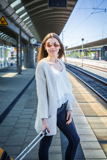 Full length of woman standing with luggage at railroad station platform