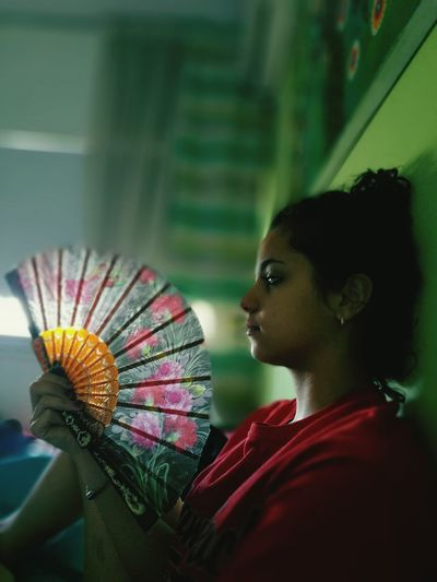 Close-up of woman holding fan