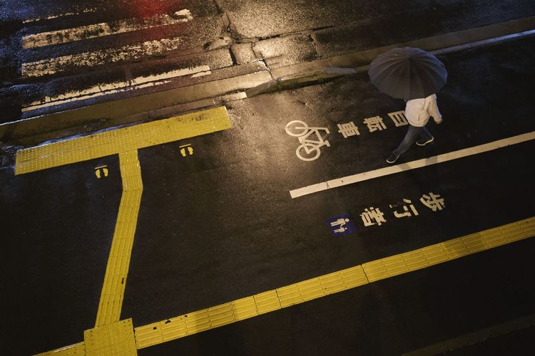 Umbrella Rain People Western Script Text Communication High Angle View Sign Symbol No People Yellow Road Road Marking Street City