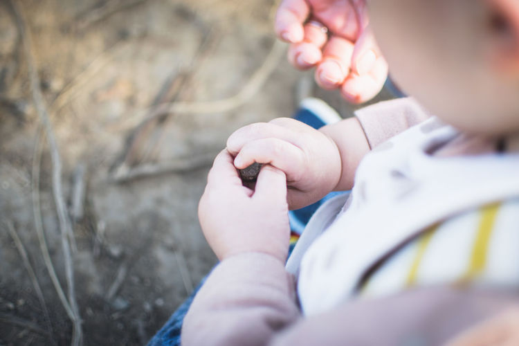 High angle view of baby holding stone in hands