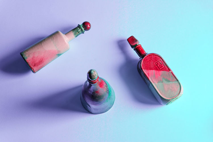 High Angle View Of Painted Bottles Over Colored Background