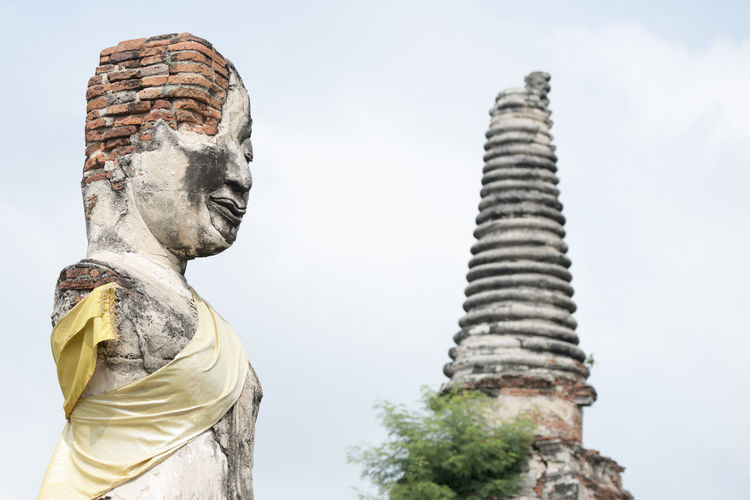 Low Angle View Of Damaged Sculpture By Temple Against Sky
