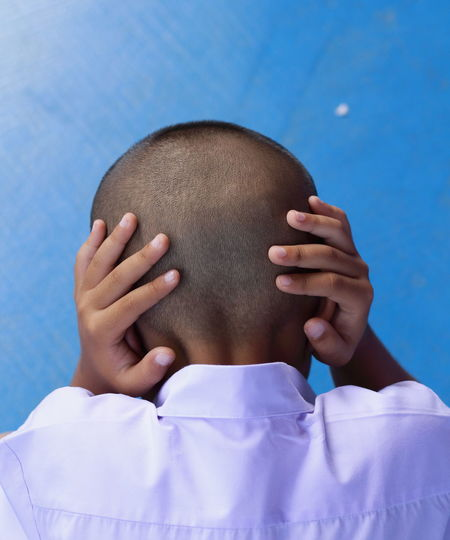Rear view of boy covering ears against blue wall
