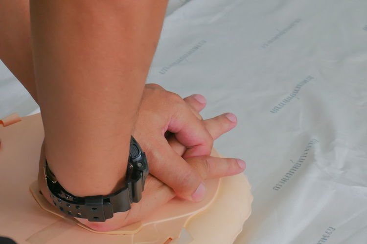 Cropped hands of paramedic practicing cpr on mannequin