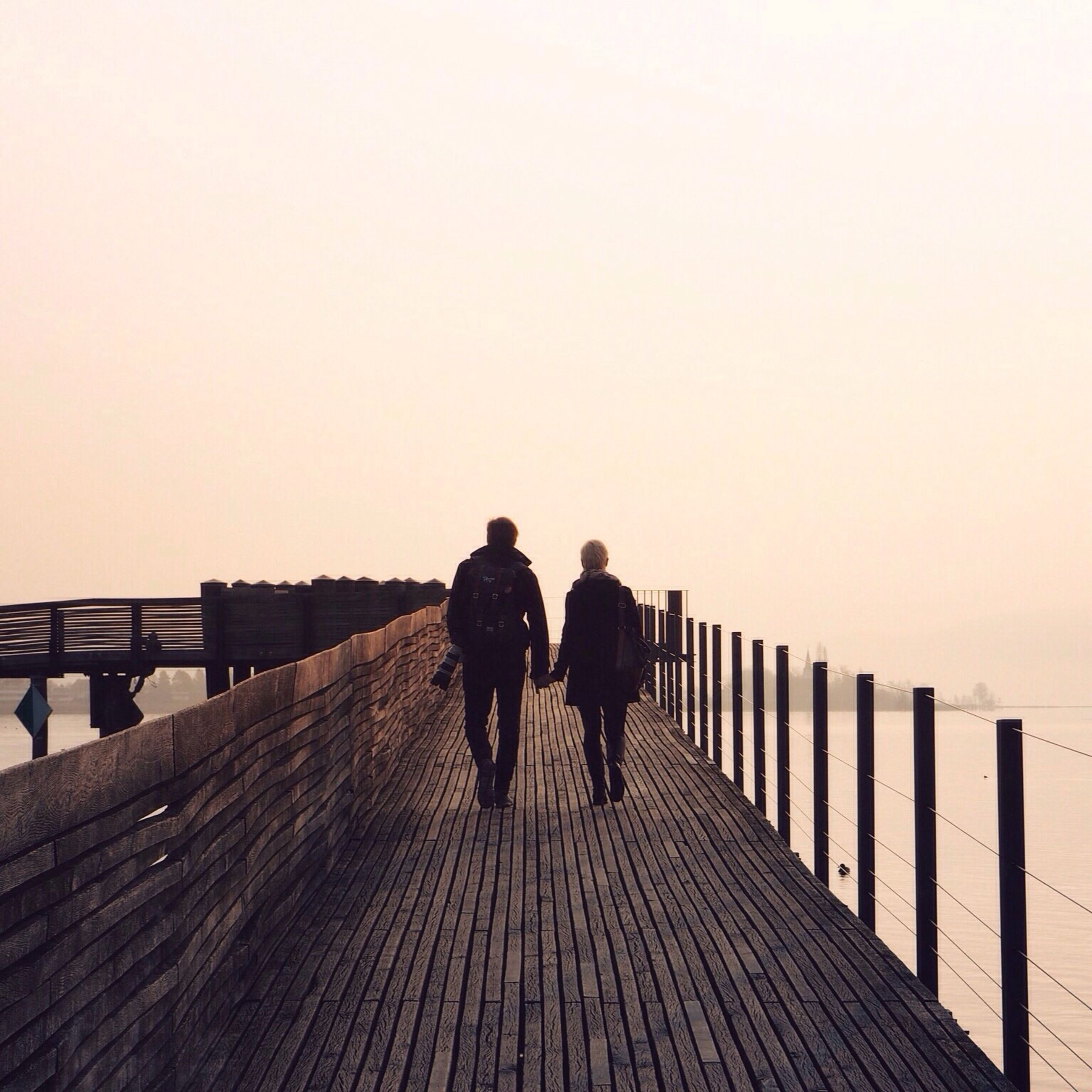 men, clear sky, railing, lifestyles, copy space, walking, full length, leisure activity, rear view, togetherness, person, the way forward, pier, silhouette, connection, standing, sea, boardwalk