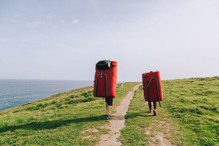 People With Mattress Walking At Beach Against Sky